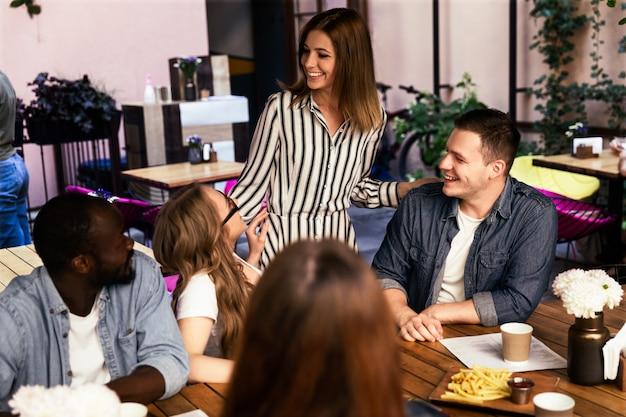 Молодые люди болтают и смеются за ресторанным столом на террасе