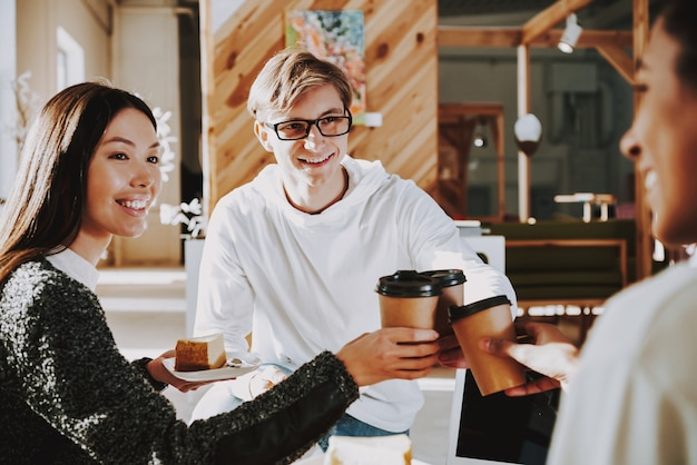 Young people are drinking coffee in office with friends