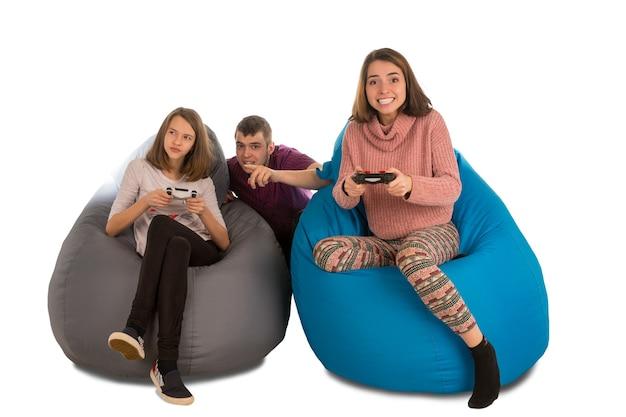 Молодые люди с энтузиазмом играют в видеоигры, сидя на сине-серых креслах-мешках для гостиной или другой комнаты, изолированной на белом