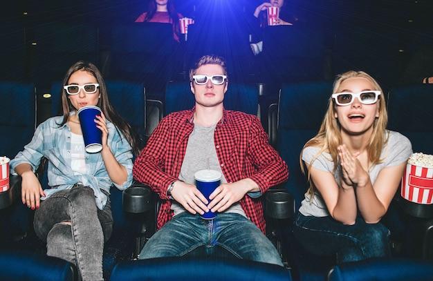 젊은이들은 영화관의 의자에 앉아 있다. 그들은 영화를 볼 때 안경을 쓴다. 남자는 콜라 한 잔을 가지고 있고 여자는 팝콘 바구니를 가지고 있습니다. 그들은 영화를 보고 있다. 금발 소녀는 카메라를 찾고