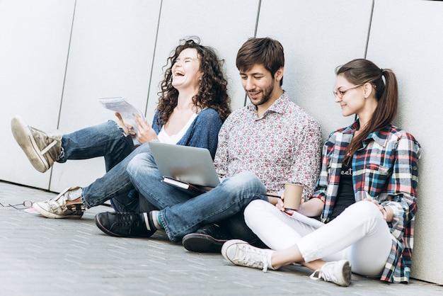 젊은 사람들은 다른 도구를 사용하고 벽 근처에 앉아 웃고 있습니다. 랩톱 컴퓨터를 사용하여 공부하는 학생들. 교육 소셜 미디어 개념.