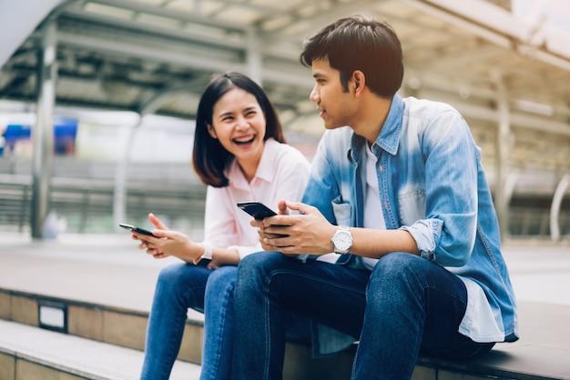 若い人たちは、スマートフォンを使用し、自由な時間に座っている間笑顔しています。技術コンセプト