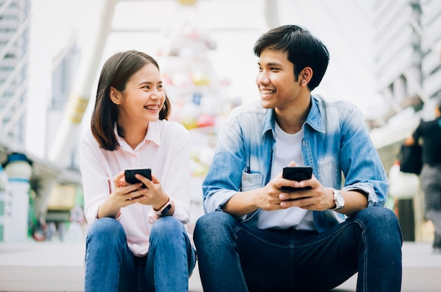 Young people are using smartphone and smiling while sitting on free time.