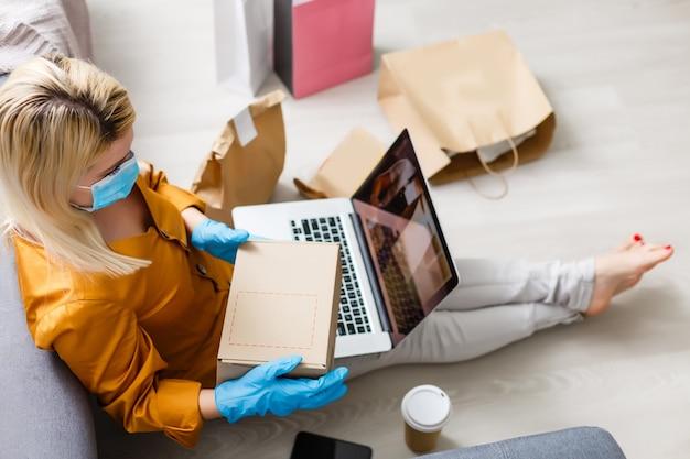 自宅での若者は、製品のオンライン配信を自己検疫で注文します。在宅勤務の検疫。コロナウイルス分離によるマスクされた家族の新生活。コンピューターでのリモート作業。パンデミックライフスタイル