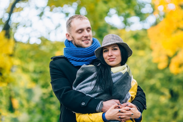 Young people in autumn park. yellow trees and leaves. happy young family concept.