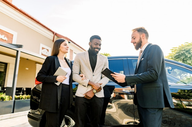 Young people business couple african man and caucasian woman standing outdoors in a car rental service, talking with young man manager. auto service concept