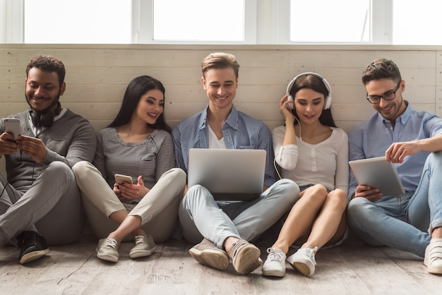 Young people in casual clothes using gadgets