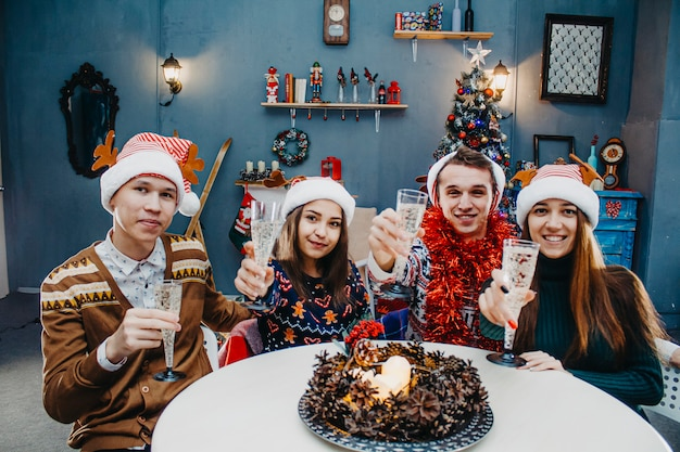 Young people celebrate christmas holidays at the table.