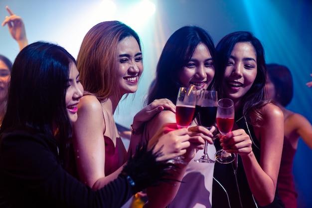 Молодые люди празднуют вечеринку, выпивают и танцуют