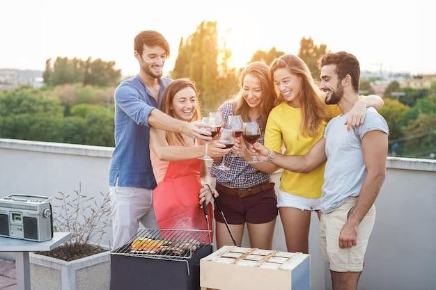 테라스에서 야외 바베큐 파티에서 와인을 응원하는 젊은 사람들-와인 잔에 초점