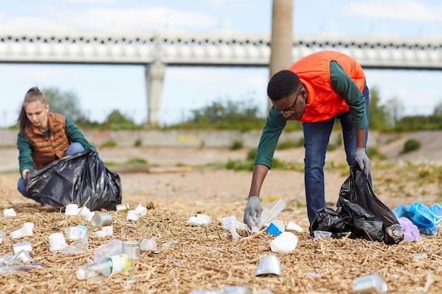 屋外で地面を掃除する若者たちは、ゴミをバッグに拾い上げます