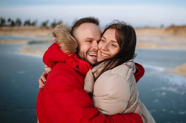 クローズアップでお互いにしがみついている若者。冬、凍った湖でダウンジャケットを着た男の子と女性が押し付け合う