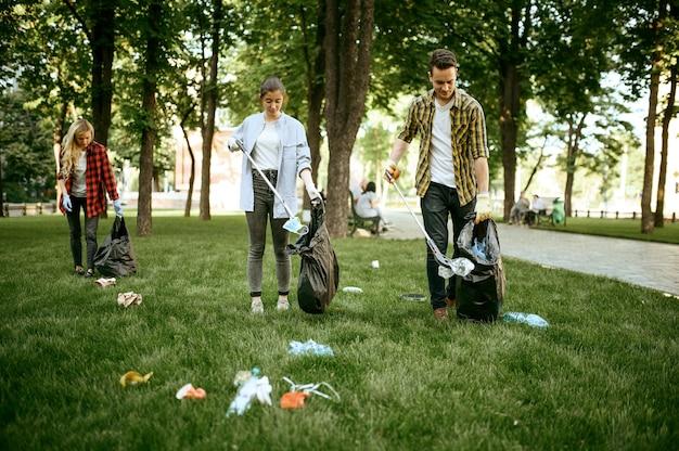 Молодые люди собирают мусор в полиэтиленовые пакеты в парке, занимаются волонтерством