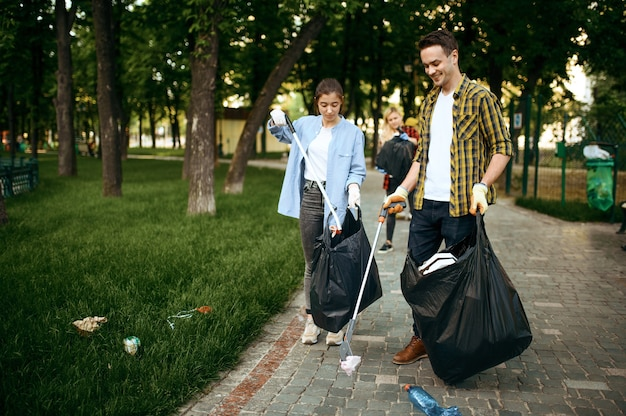 Young people collects trash in plastic bags in park, volunteering. volunteers cleans forest, ecological restoration, garbage collection and recycling, ecology care, environment cleaning