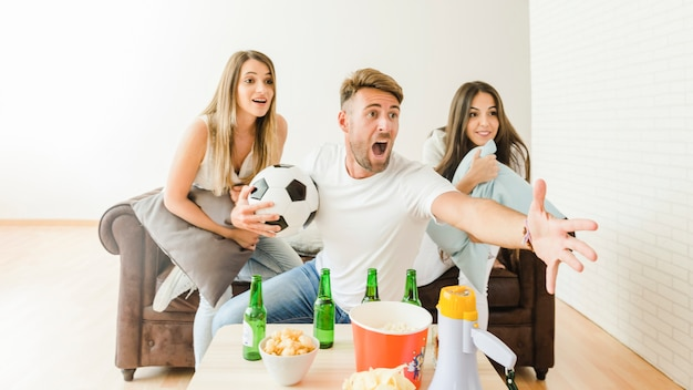 Young people on couch watching soccer game