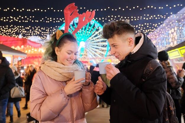 Молодые люди, пара подростков веселятся на рождественской ярмарке, пьют горячий чай из кружек