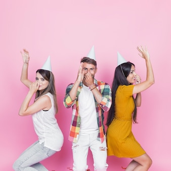 Young people dancing on pink background