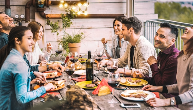 Young people dining and having fun drinking red wine together on balcony rooftop dinner party - happy friends eating bbq food at restaurant patio - millannial life style concept