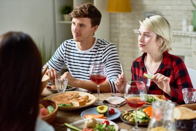 Молодые люди обедают с друзьями дома