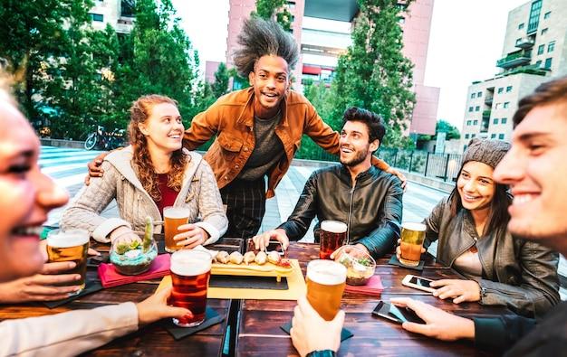 양조장 바 dehor에서 맥주를 마시는 젊은 사람들