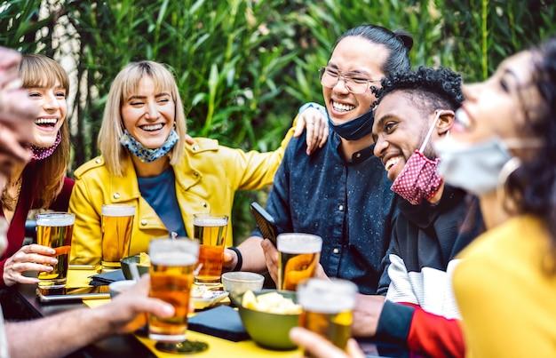 Молодые люди пьют пиво с открытой маской для лица - новая концепция нормального образа жизни, когда тысячелетние друзья веселятся вместе в счастливый час на вечеринке в саду пивоварни