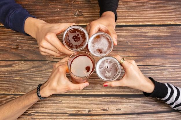 ビールを飲み、木製のテーブルで楽しい時間を過ごす若者