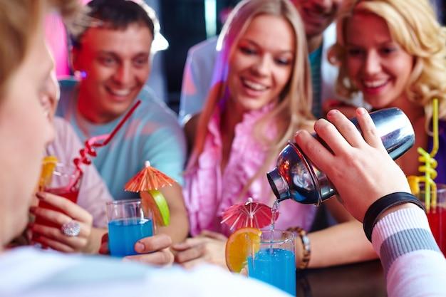 Молодые люди пьют коктейли в ночном клубе