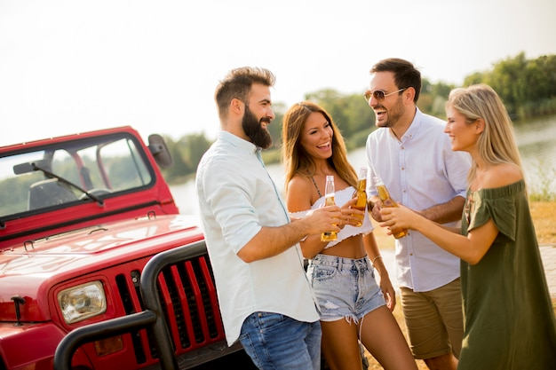 Young people drinking and having fun by car