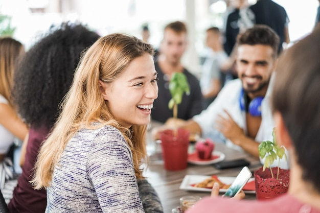 젊은 사람들은 아침 식사를 먹고 바 레스토랑에서 스무디를 마시는-여자 얼굴에 초점