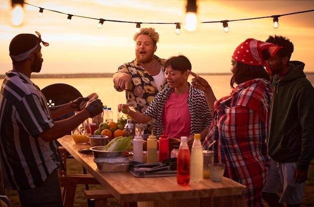 Молодые люди едят фаст-фуд за столом во время пляжной вечеринки на открытом воздухе