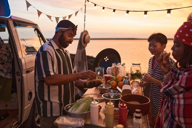 Young people eating fast food while young man preparing it for them during beach party