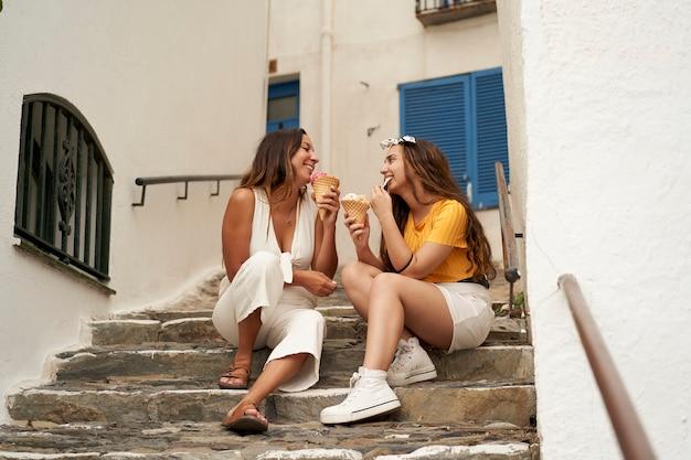アイスクリームを食べて、きれいな村の階段に座って笑っている若者たち。