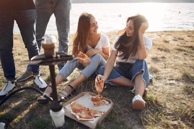 若者がビーチでピザを食べて、シーシャを吸う