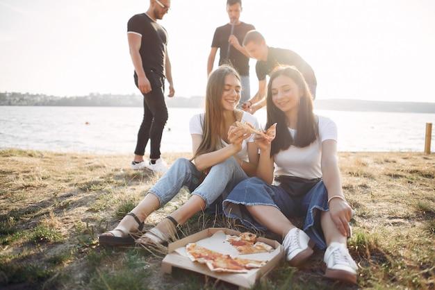 Молодые люди едят пиццу и курят кальян на пляже