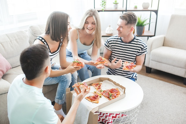 Молодые люди едят пиццу. группа друзей, обедающих в помещении. веселые друзья вместе.