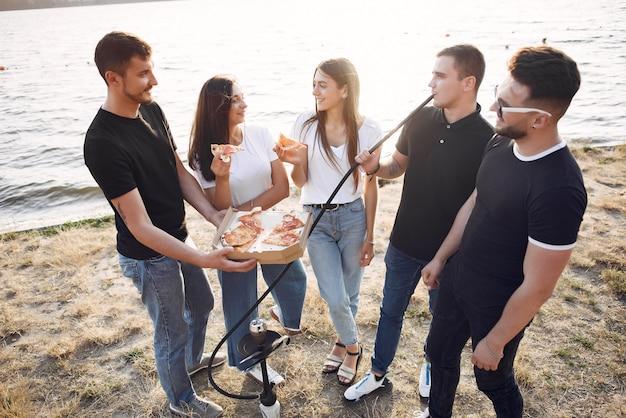 Young people eating pizza and smoking shisha at the beach
