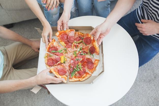 Молодые люди едят пиццу сверху. группа друзей, обедающих в помещении. веселые друзья вместе.