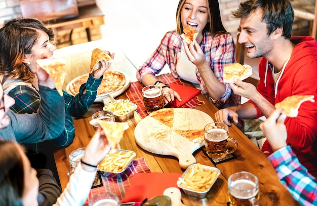 Young people on eating takeaway pizza at home on family reunion - friendship life style concept with happy friends enjoying time together having fun at pizzeria drinking brew pint - warm bright filter