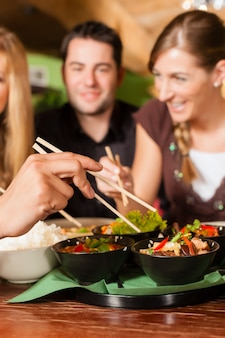Young people eating in thai restaurant