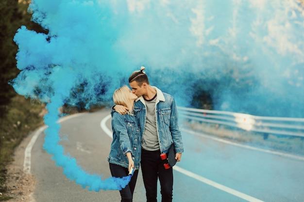 Молодые люди обнимаются и целуются с красочным синим дымом в руке.