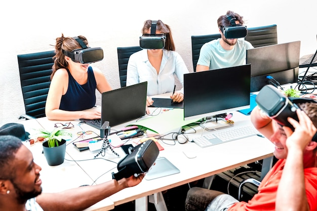 Young people employee workers having fun with vr virtual reality goggles in startup office - human resource business concept at alternative studio coworking time