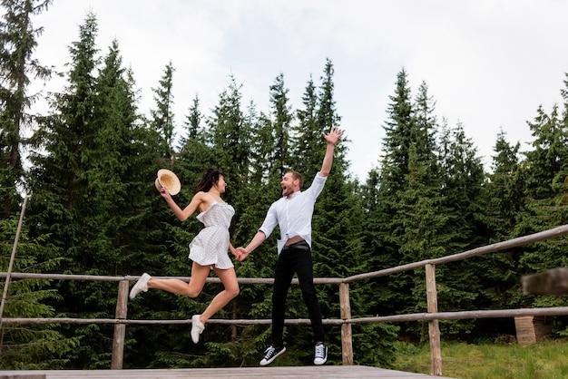 Молодежь любит летние каникулы в лесу. пара веселится на деревянной веранде
