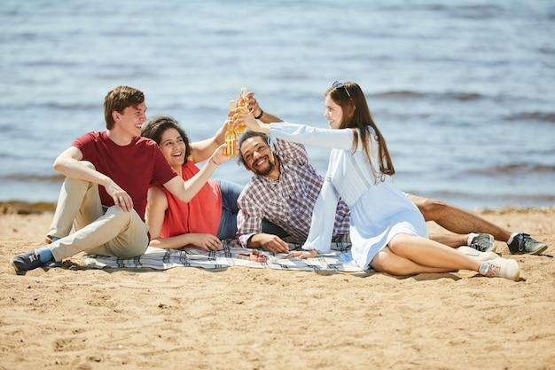 Young people enjoying picnic on beach