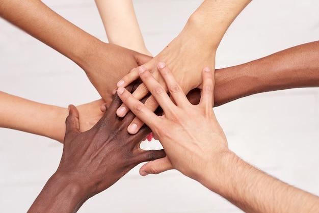 젊은이들은 손을 접습니다. 화합과 팀워크를 보여주는 손 더미를 가진 다국적 친구들.