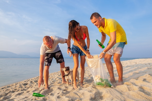 Young people friends picking up trash and garbage on tropical beach saving planet and ecology in indonesia, thailand and philippines