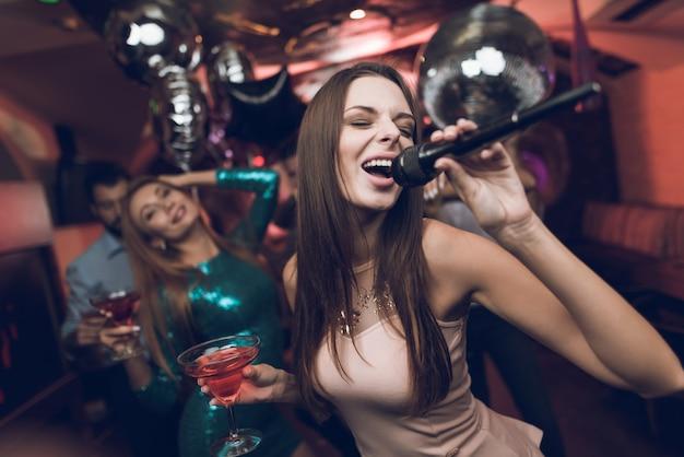 Молодые люди веселятся в ночном клубе и поют в караоке