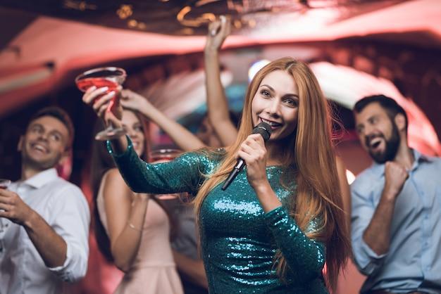 Молодые люди веселятся в ночном клубе и поют в караоке.
