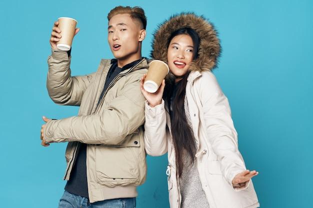 Молодые люди веселятся на синем за чашкой кофе