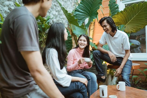 카페에서 즐거운 시간을 보내고있는 젊은 사람들. 웃 고 앉아 커피를 마시고 함께 즐기는 친구