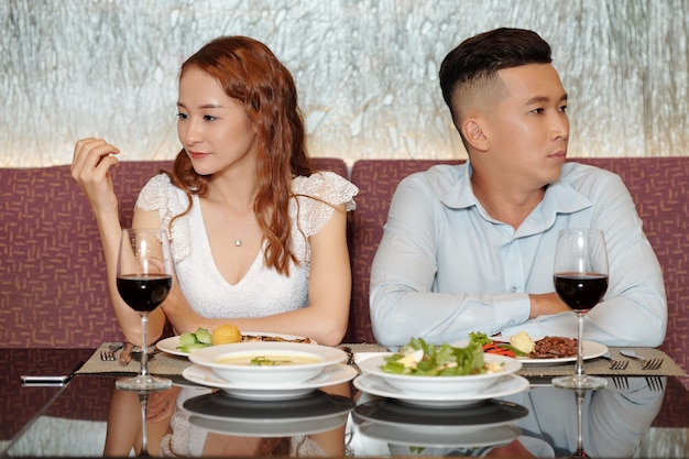 Young people having bad first date, they are sitting at restaurant table, not talking and looking in different directions